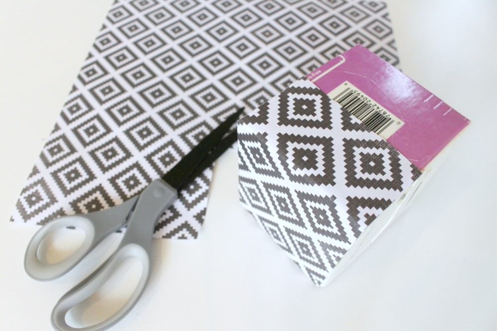 cut out pieces of scrapbook paper being used to cover a small cardboard box